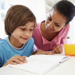young boy doing homework with help of his mother